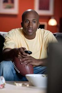 man-watching-tv-holding-football