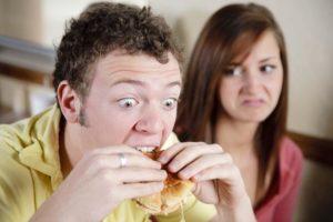 man eating burger, girl pissed