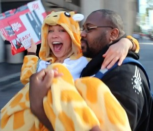 GiGi getting carried by a stranger in a giraffe costume